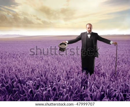 Portrait of a gentleman with cylinder hat standing on a purple meadow