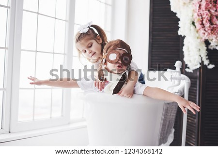 Portrait of a girl and a boy in pilot hat playing in bathroom at pilots or sailors. The concept of travel, childhood and the realization of dreams. #1234368142