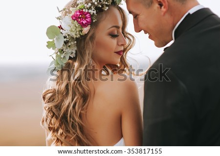 portrait of a girl and couples looking for a wedding dress, a pink dress flying with a wreath of flowers on her head on a background tsvetu chicago garden and the blue sky, and they hug and pose