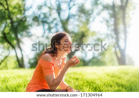 Portrait of a girl blowing a dandelion at sunset