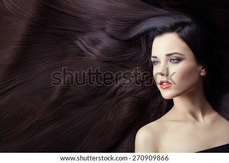 Portrait of a girl brunette closeup. She is lying on her long hair. Hair very much.