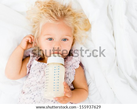 Portrait of a girl drinking from her baby bottle