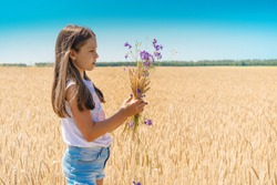 Portrait of a girl holding wild flowers in a meadow Field of rye at sunset