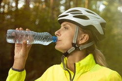Portrait of a girl in a bright green windbreaker, helmet and glasses who drinks water in the forest