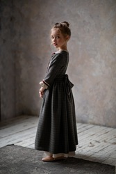 Portrait of a girl in a gray vintage dress. Romantic image of a girl. Image with selective focus.