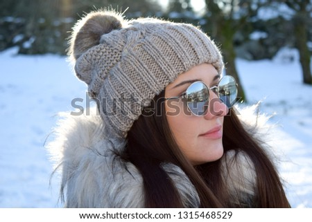 Portrait Of A Girl In A Hat With A Pompon Against The Background Of A Winter