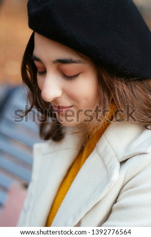 d472c08154a239 Portrait of a girl in a light coat, yellow sweater and black beret on gray
