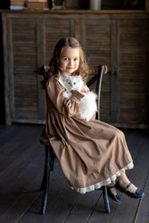 Portrait of a girl in a vintage dress. A girl with long hair in a brown dress with a white collar. The girl is holding a white kitten in her arms. Image with selective focus.