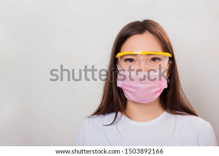 Portrait of a girl in a white coat, mask and glasses. Photo on a white background.