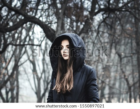 Portrait of a girl in black clothes. Girl in the paranormal world. Strange forest in a fog. Mystical atmosphere. Dark wood. Mysterious road. Gothic witch. Background wallpaper. Gloomy times