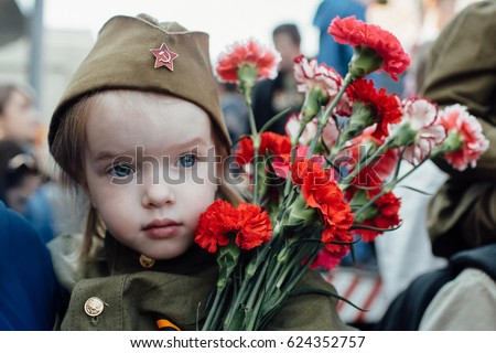 Portrait of a girl in military uniform with flowers on May 9 #624352757
