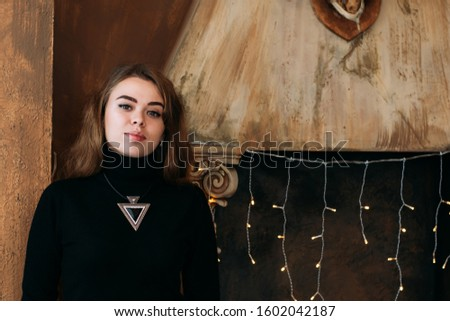 Portrait of a girl in the studio. New Year. Against the background of a fireplace with a garland. copy space. copy space 2020 2021 2022 2023