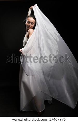 Portrait of a girl in white raiment dancing in semidarkness