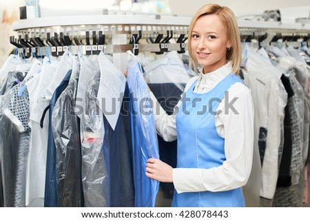 Portrait of a girl Laundry worker on the background of the coat racks at the dry cleaners
