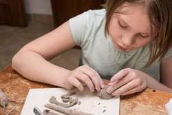 Portrait of a girl making precise patterns on a piece of clay - a ceramic workshop - creative leisure time