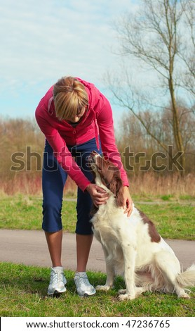 Portrait of a girl playing outdoors with a dog.