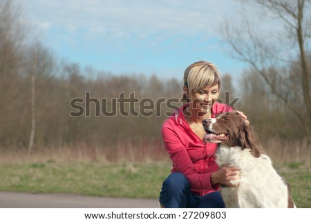 Portrait of a girl playing with a dog outdoors.