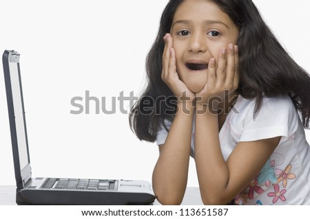 Portrait of a girl sitting in front of a laptop in shock