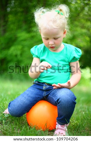 portrait of a girl sitting on the ball in the park