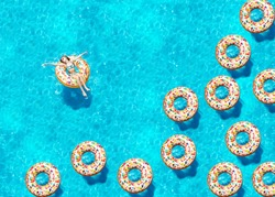 Portrait of a girl swim on inflatable candy doughnut buoys in the swimming pool view from above