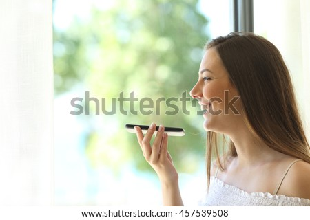 Portrait of a girl using the voice recognition of the phone and looking through a window of a house #457539508