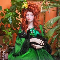 Portrait of a girl with a beautiful hairstyle in the rococo style in a green royal dress. Renaissance hairstyle. Red-haired young woman with black cat. Indoors shot in the Marie Antoinette style.