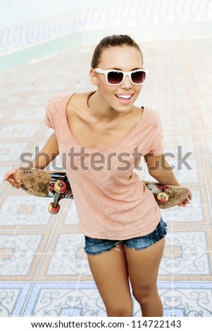 Portrait of a girl with a skateboard in her hand, outdoors