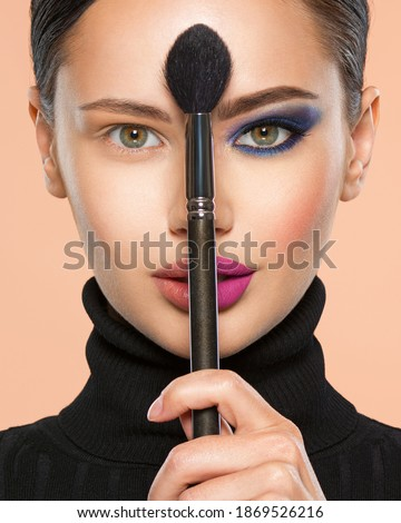 Portrait of a girl with cosmetic brush at face. Woman holds a big makeup brush right in the middle of the face. One half face of a beautiful white woman with  bright makeup and the other is natural.