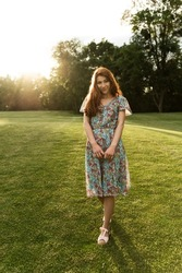 portrait of a girl with freckles and red hair. sunset. joyful girl at sunset of the day. summer dress and cheerful mood. portrait of a girl. unique appearance