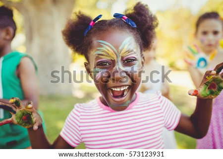 Portrait of a girl with make-up showing her painted hands in a park