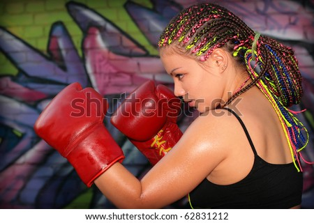 Portrait of a girl with red boxing gloves over graffiti background