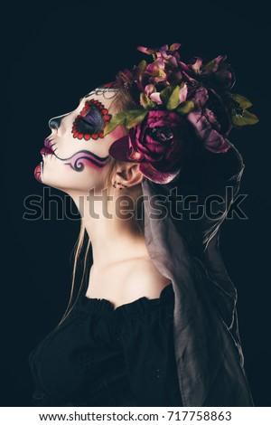 Stock Photo Portrait of a girl with sugar skull makeup over black background. Calavera Catrina. Dia de los muertos. Day of The Dead. Halloween.