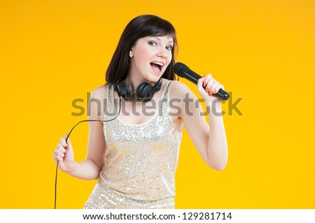 Portrait of a glamorous caucasian girl holding mike and singing