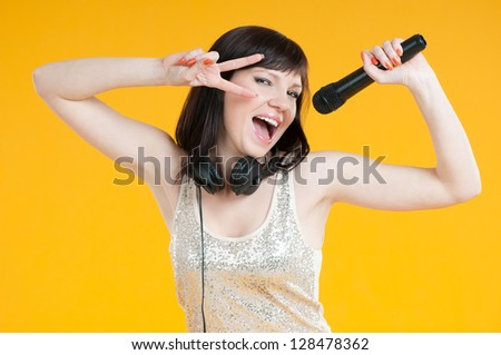 Portrait of a glamorous girl holding a microphone and singing