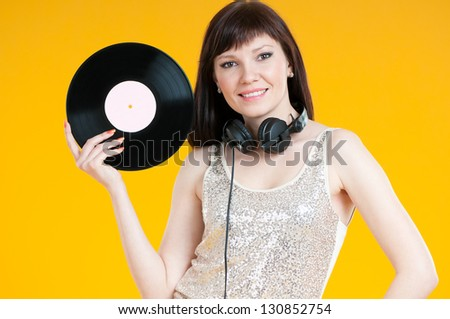 Portrait of a glamorous girl holding a vinyl record and smiling
