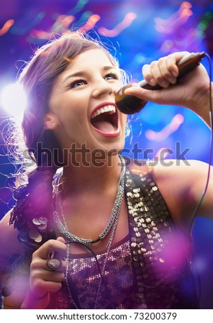 Portrait of a glamorous girl with mike singing song