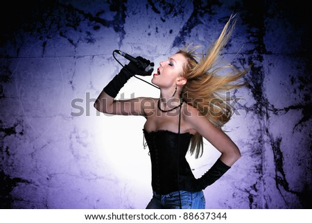Portrait of a glamorous singer girl holding a mike and singing