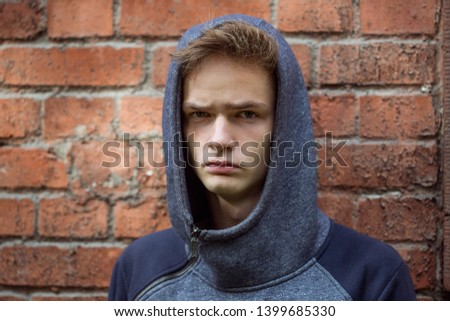 portrait of a gloomy sad teenager on a brick wall background, concept of teenage problems