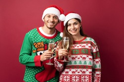 Portrait of a good looking Latin couple with ugly sweaters holding up a glass of champagne to celebrate Christmas