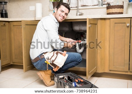 Portrait of a good looking male plumber fixing a leaky sink in a kitchen and smiling