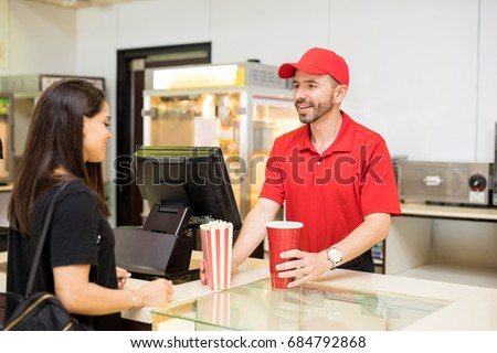 Portrait of a good looking worker in a concession food in a movie theater serving popcorn and soda to a female customer Сток-фото ©
