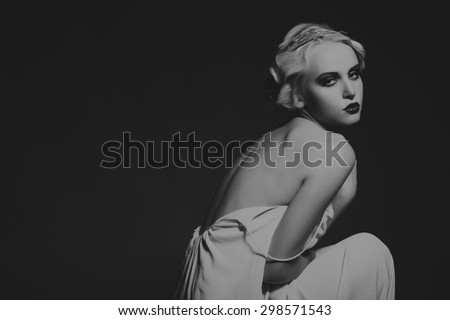 Portrait of a gorgeous blonde in a low key. The mystery, sadness, insecurity, human emotions. The girl in the style of the 20s.