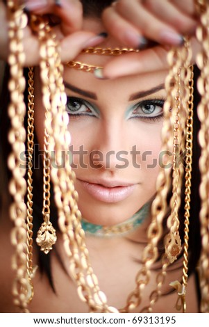 Portrait of a gorgeous brunette holding golden chains in her arms