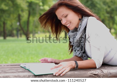 Portrait of a gorgeous brunette woman reading a book in the park