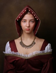 Portrait of a gorgeous girl in medieval time dress and headdress.