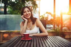 Portrait of a gorgeous happy young asian woman sitting in a cozy sidewalk cafe smiling  to the camera, attractive female enjoying sunny afternoon in modern coffee shop with amazing sunset in summer