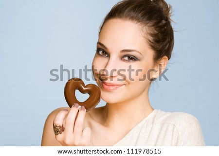 Portrait of a gorgeous happy young brunette woman holding heart shaped cookie.