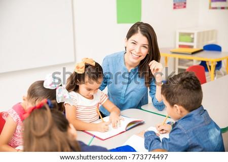 Portrait of a gorgeous Hispanic preschool teacher teaching her students in a classroom