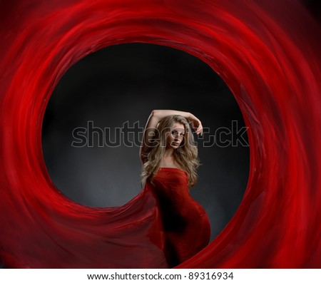 Portrait of a gorgeous sexy blonde with long beautiful hair and body wrapped in red silk, like a flower