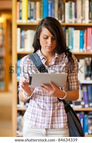 Portrait of a gorgeous student using a tablet computer in a library